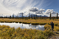 USA, Alaska, Tourist taking photograph of landscape in autumn - FOF004472