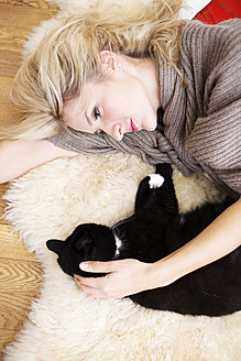 Young woman with cat lying on carpet - VRF000108