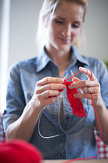 Young woman knitting with red yarn - VRF000099