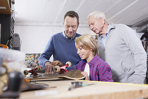 Germany, Leipzig, Grandfather, father and son repairing skateboard - BMF000580
