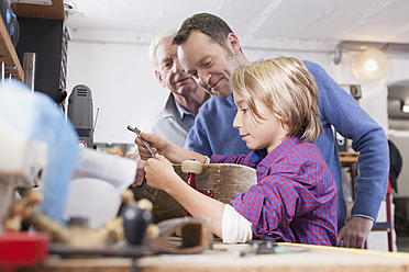 Germany, Leipzig, Grandfather, father and son repairing skateboard - BMF000583