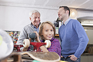 Germany, Leipzig, Grandfather, father and son repairing skateboard - BMF000589