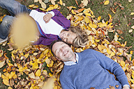 Germany, Leipzig, Father and son lying on leaves, smiling - BMF000631