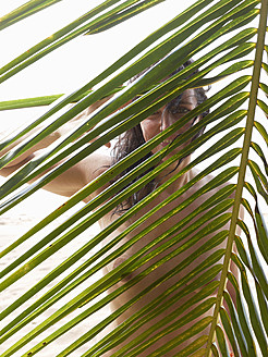 Central America, Costa Rica, Woman peeking from palm leaves at Punta Uva - BSC000198