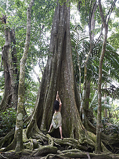 Central America, Costa Rica, Woman posing at Kapok Tree in rainforest - BSCF000200