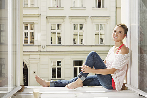 Germany, Berlin, Young woman sitting at open window, smiling, portrait - SKF000963