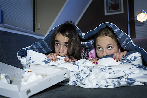 Girls hiding under bed sheet while watching scary film - RNF001089