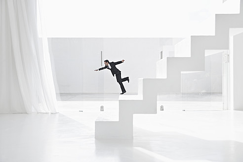 Spain, Businessman falling down from ladders - PDYF000296