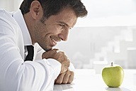 Spain, Businessman looking at apple, smiling - PDYF000332