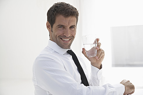 Spain, Businessman holding water glass, smiling, portrait - PDYF000338