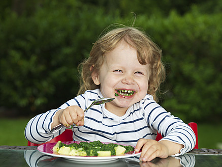 Germany, Duesseldorf, Girl sitting outside and eating spinach, smiling, portrait - STKF000044