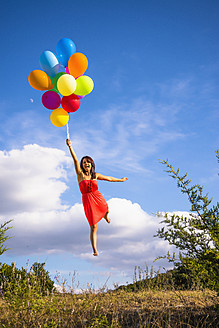 USA, Texas, Young woman flying with balloons - ABAF000391