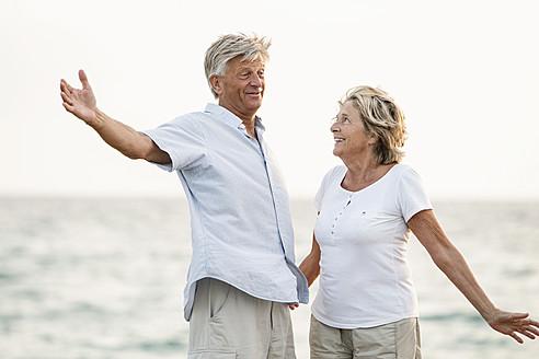 Spain, Senior couple having fun at the sea - JKF000011