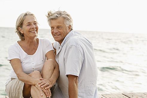 Spain, Senior couple sitting at the sea, smiling - JKF000014