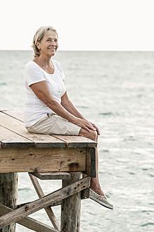 Spain, Senior woman sitting on jetty at the sea - JKF000035