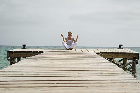 Spain, Senior woman doing yoga on jetty at the sea - JKF000041