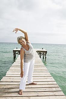 Spain, Senior woman doing yoga on jetty at the sea - JKF000044