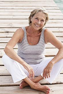 Spain, Senior woman sitting on jetty at the sea - JKF000047