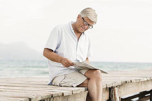 Spain, Senior man reading newspaper on jetty at the sea - JKF000053