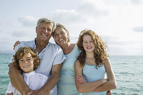 Spain, Grandparents with grandchildren at the sea, smiling, portrait - JKF000062