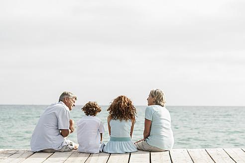 Spain, Grandparents with grandchildren sitting on jetty - JKF000071