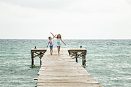 Spain, Girl and boy running on jetty at the sea - JKF000074