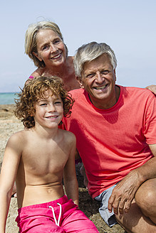 Spain, Grandparents with grandson sitting on beach, smiling - JKF000094