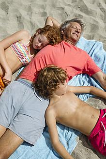 Spain, Grandfather and grandchildren relaxing on beach - JKF000097