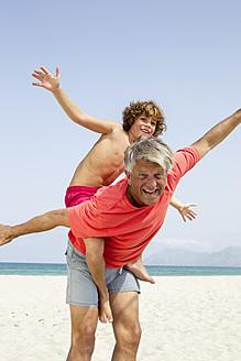 Spain, Grandfather giving piggyback ride to grandson, smiling - JKF000106