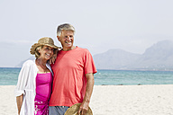 Spain, Senior couple standing at beach, smiling - JKF000112
