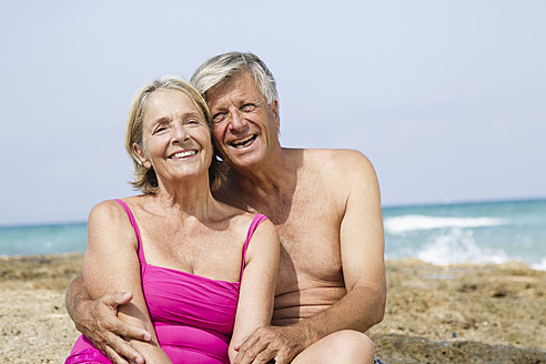 Spain, Senior couple sitting on rock at beach, smiling - JKF000118