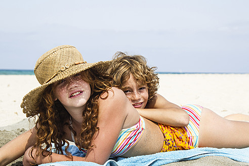 Spain, Brother and sister having fun on beach - JKF000124