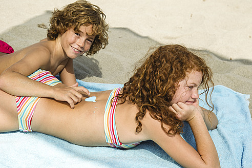 Spain, Brother drawing on sisters back with suncream - JKF000127