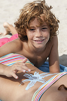 Spain, Brother drawing on sisters back with suncream - JKF000130