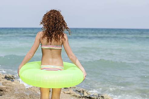 Spain, Girl with swim ring on beach - JKF000139