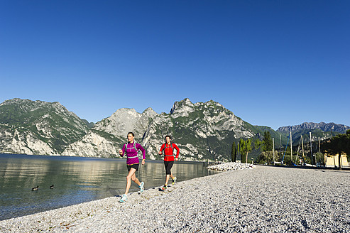 Italy, Mid adult couple jogging by Lake Garda - MIRF000512