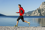 Italy, Mid adult man jogging by Lake Garda - MIRF000518