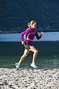 Italy, Mid adult woman jogging by Lake Garda - MIRF000521