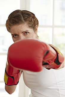 Germany, Duesseldorf, Portrait of mature woman with boxing gloves - STKF000102