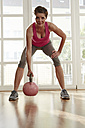 Germany, Duesseldorf, Mature woman exercising with kettlebell - STKF000109