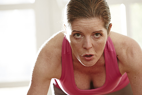 Germany, Duesseldorf, Mature woman doing push ups at home - STKF000114