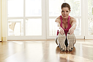 Germany, Duesseldorf, Mature woman exercising at home - STKF000116