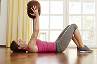 Germany, Duesseldorf, Mature woman exercising with medicine ball - STKF000132
