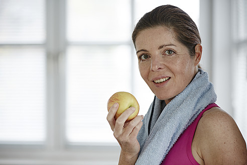 Germany, Duesseldorf, Mature woman eating apple, smiling - STKF000139