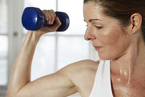 Germany, Duesseldorf, Mature woman exercising with barbell at home - STKF000166