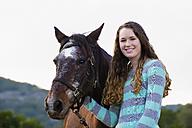 USA, Texas, Teenage girl standing with Quarterhorse, smiling, portrait - ABA000552