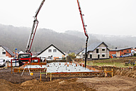 Europe, Germany, Rhineland-Palatinate, Construction workers filling concrete in casing for foundation - CSF016009