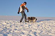 Germany, Bavaria, English Springer Spaniel and dog owner playing in snow - MAEF005447
