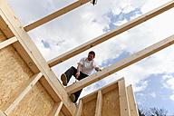 Europe, Germany, Rhineland Palatinate, Man standing on roof beam - CSF016068