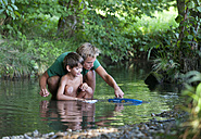 Austria, Friends playing with boat in stream, smiling - WWF002742